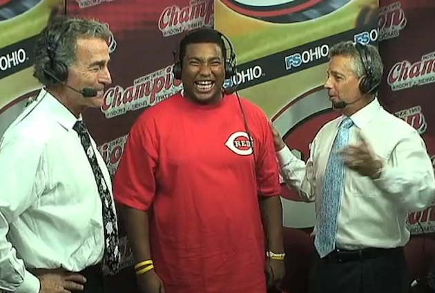 Reds fan Caleb Lloyd visits with the team's broadcasters on Monday. (MLB.TV)