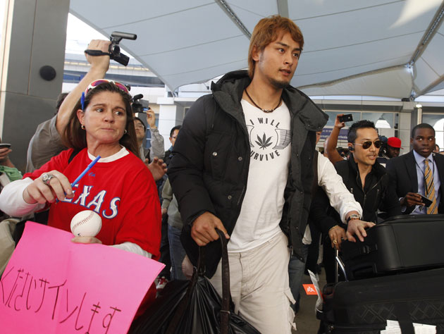Yu Darvish's choice of clothing for his arrival in Texas on Friday was rather curious. (AP)