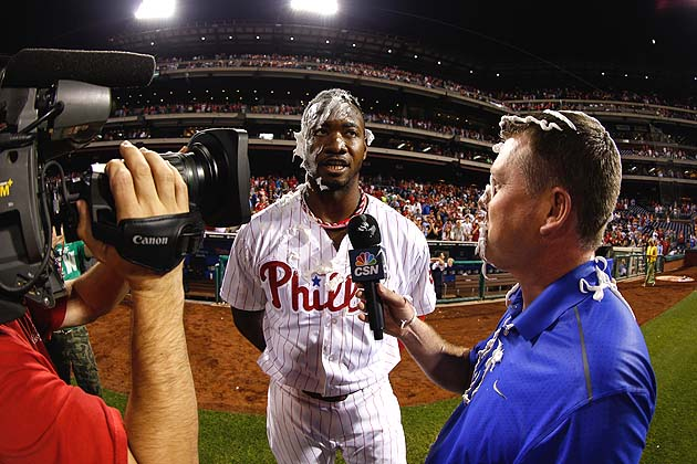 The white stuff on Domonic Brown and the TV reporter is the residue of victory. (Getty)
