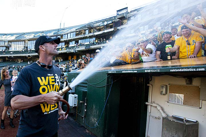 The A's win the division, so fans in Oakland get the hose from Grant Balfour. (Getty)