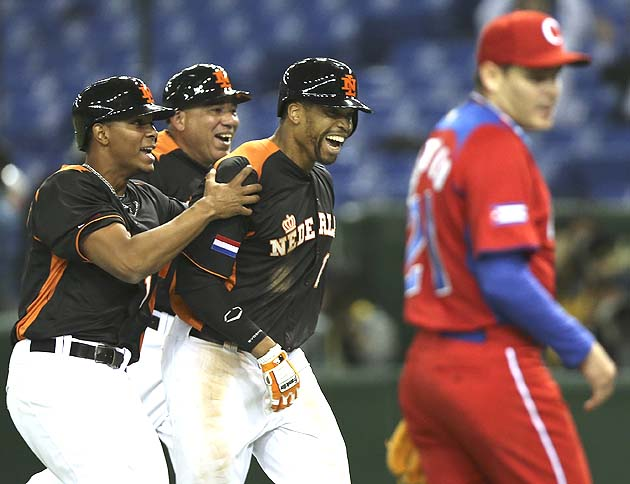 Kalian Sams (center) grabbed by teammate Xander Bogaerts with coach Wirn Martinus. Cuba's pitcher is Diosdany Castillo. (AP)