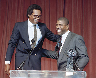 Oh, that Rod Carew. The Hall of Famer stands on a step stool to tower over Magic. (AP)
