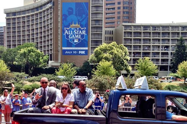Derek Jeter waves at fans as he rides with his parents in the All-Star parade. (Big League Stew)