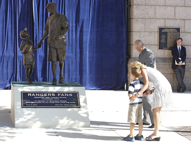 Jenny and Cooper Stone look at the 'Rangers Fans' statue on Thursday as Nolan Ryan looks on. (AP)