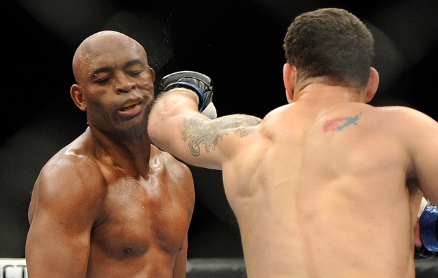 Chris Weidman (R) lands a left that knocks out Anderson Silva at UFC 162 (AP)