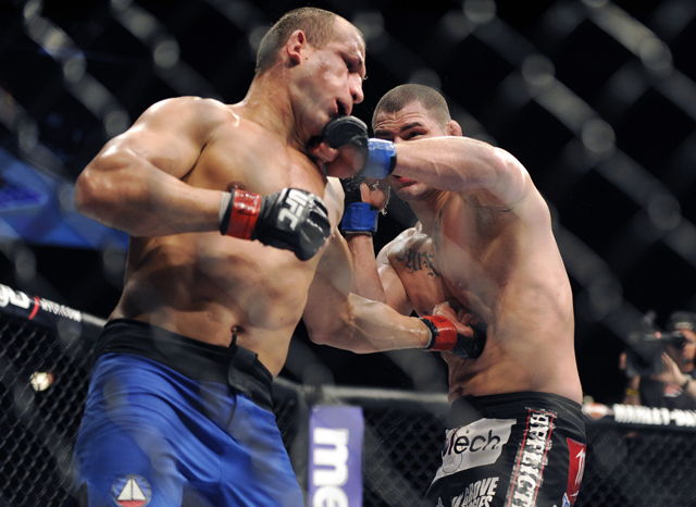 Cain Velasquez (R) lands a punch on Junior dos Santos at UFC 155 in 2012 (AP)