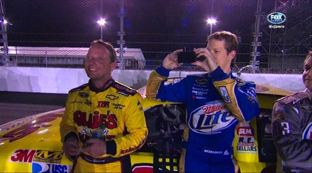 Brad Keselowski works his cell phone as Dave Blaney looks on.