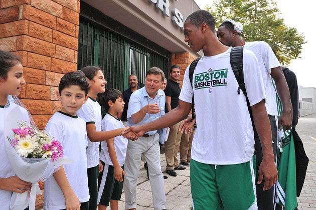 Rajon Rondo welcomes children to a Connect Four demolition (Brian Babineau/ Getty).