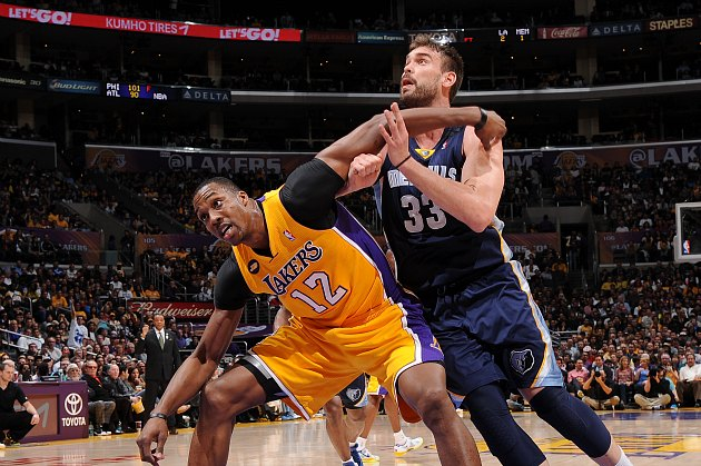 Dwight Howard searches for leverage against Marc Gasol (Andrew D. Bernstein/ Getty).