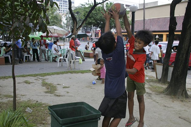 Two young Manila residents play one-on-one at a trash can (Paula Bronstein/ Getty).