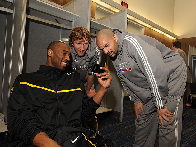 Kobe shows Dirk and Carlos how many favs his last joke got. (Andrew D. Bernstein/NBA/Getty Images)