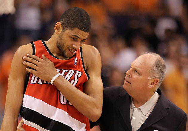 Nicolas Batum discusses shoulder pain with Trail Blazers athletic trainer Jay Jensen. (Getty Images)