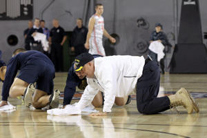 Marquette coach Buzz Williams wipes up a wet spot Friday (Getty Images)