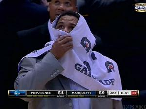 Providence coach Ed Cooley shields himself from the bat (screengrab via @BubbaProg)