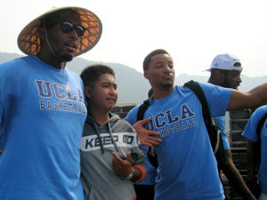 Joshua Smith (left) and Norman Powell (right) pose with a tourist at the Great Wall (via UCLA Athletics)