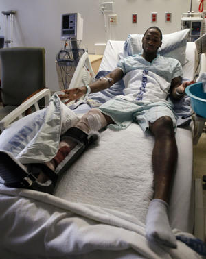 Derrick Roland looks at his surgically repaired right leg in Dec. 2009 (AP)