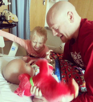 Chris and Kacee visit with Avery in his hospital bed (via @ChrisHarriman24)