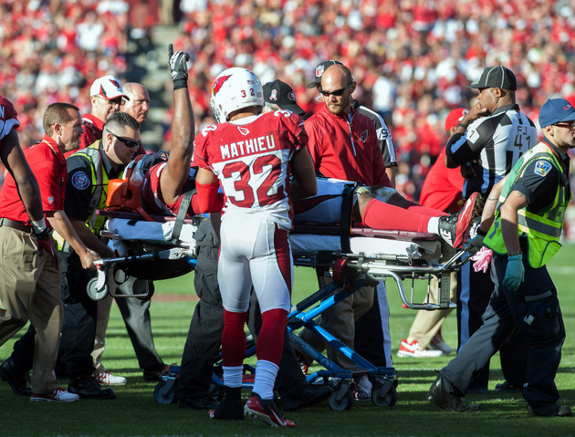 Tyrann Mathieu checks in on an injured Calais Campbell (USA Today Sports Images)