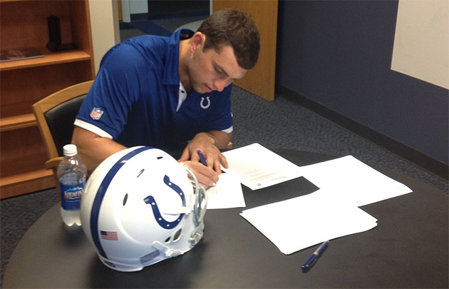 Luck signs his new contract. Perhaps he can buy a few books for the room. (@JimIrsay)