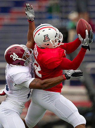 Arizona receiver Juron Criner goes over Alabama's Dequan Menzie to make a catch. (AP)