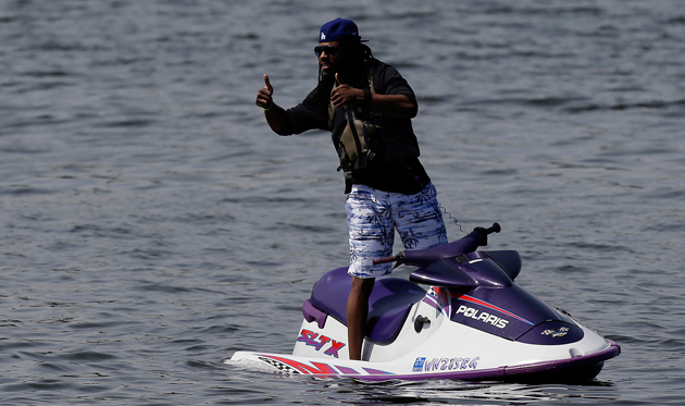 Richard Sherman eggs his new teammates on from Lake Washington. (AP)