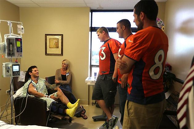 Chris Kuper, Ben Garland, and Jacob Tamme with Aurora shooting survivor Carey Rottman. (DenverBroncos.com)