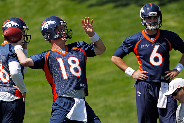 Peyton Manning airs it out during Monday's practice while rookie QB Brock Osweiler looks on. (AP)