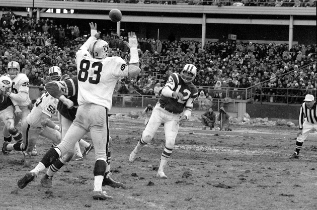 Joe Namath throws the ball over big Ben Davidson in the 1968 AFL playoffs. (AP)