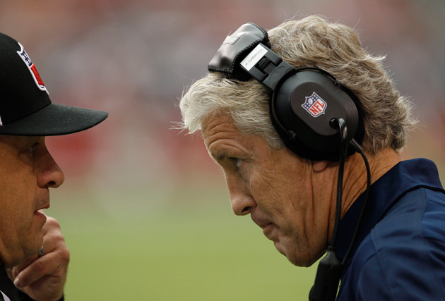 Seahawks head coach Pete Carroll speaks with an official of unknown origin. (AP)