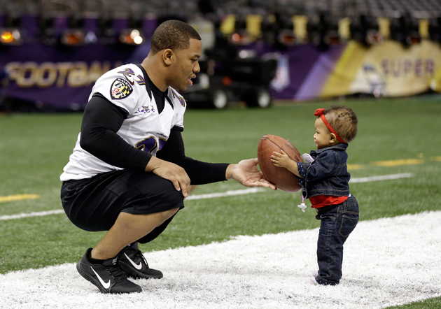 Ray Rice hands a football to his daughter, Rayven, during Saturday's informal practice. (AP)