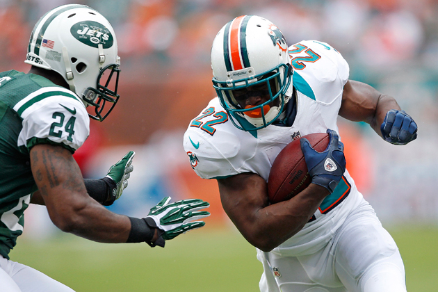 Reggie Bush drops a shoulder against Darrelle Revis last Sunday. (Getty Images)