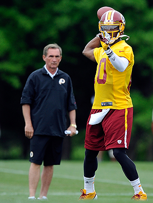 Coach 'em while you've got 'em: Mike Shanahan looks on as RGIII fires one out. (Getty Images)