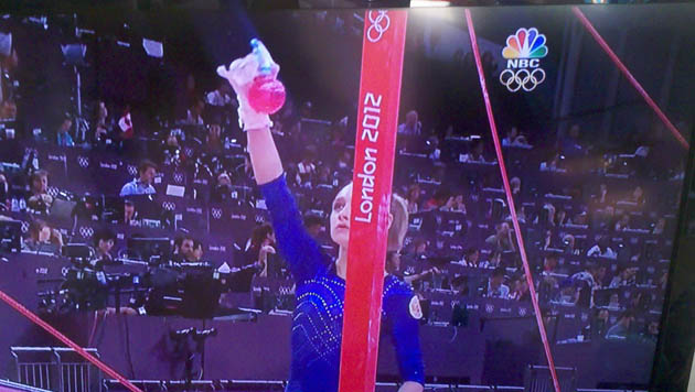 What are gymnasts spraying on the uneven bars?