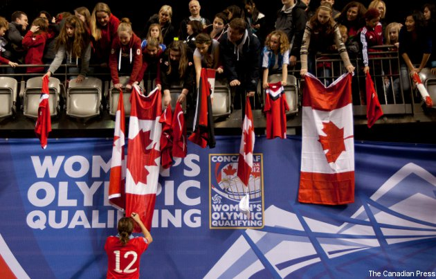Christine Sinclair signs a fan's flag after Canada's 4-0 loss to the U.S. Sunday.
