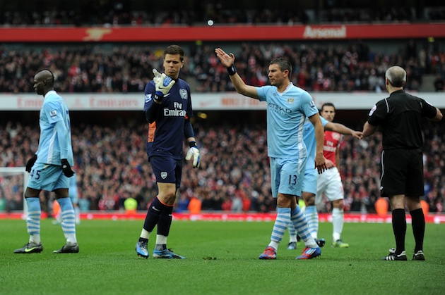 Wojciech Szczesny examines a beer bottle thrown from the stands. (Getty)