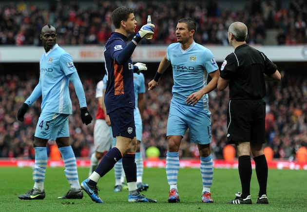 Szczesny brings the bottle to the referee's attention. (Getty)