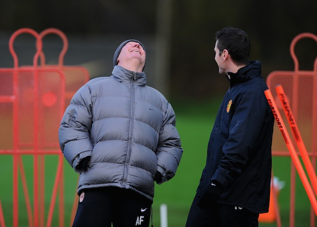 Alex Ferguson has a laugh and a neck stretch. (Getty)