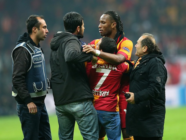 Drogba protects a pitch invader from security staff after a Champions League match. (Getty)