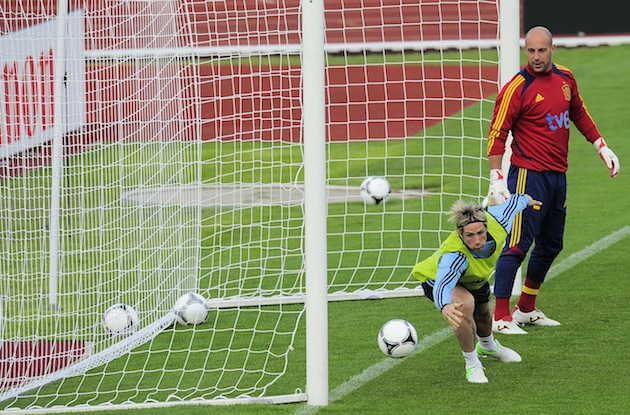 Fernando Torres attempts to save a shot while mentor Pepe Reina watches. (AP)