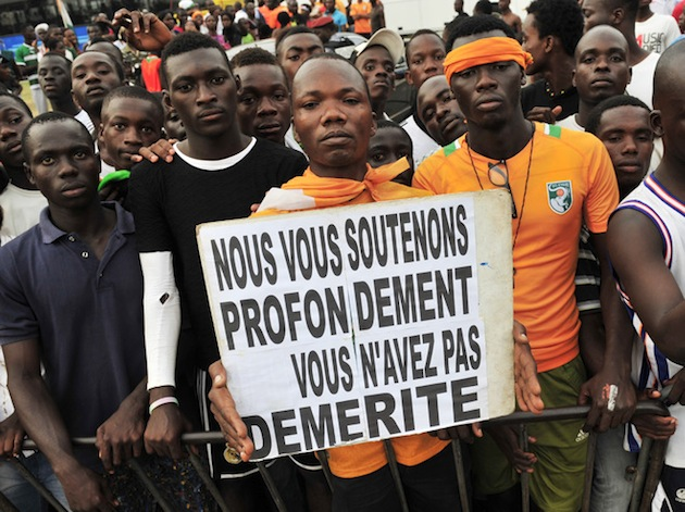 "An Ivory Coast fan holds a sign that reads ""We support you. You have no demerit."" (Getty)"