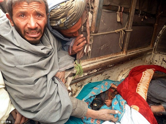 Two grieving Afghan men look at the body of a burned child killed by a U.S. soldier Sunday. (EPA/Via Daily Telegraph)