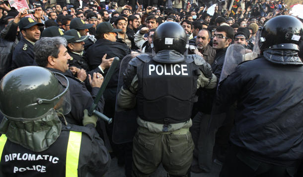 Iranian police officers scuffle with protesters trying to storm British Embassy in Tehran Tuesday. (Vahid Salemi/AP)