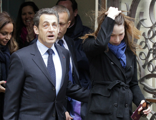 French President Nicolas Sarkozy and his wife Carla Bruni-Sarkozy leave after casting their votes in Paris, April 22, 2012. (Michel Euler/AP)