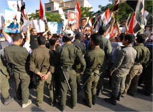 Syrian security officers surrounded pro-regime demonstrators near U.S. Embassy in Damascus in July. (Muzaffar Salman/AP)