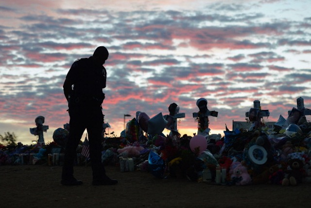 An Aurora, Colo., police officer visits the roadside memorial set up for victims. (Kevork Djansezian/Getty Images)