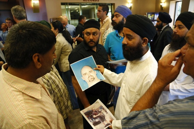 Members of the Sikh community in Wisconsin hold up a photo of the suspected gunman. (Darren Hauck/Getty)