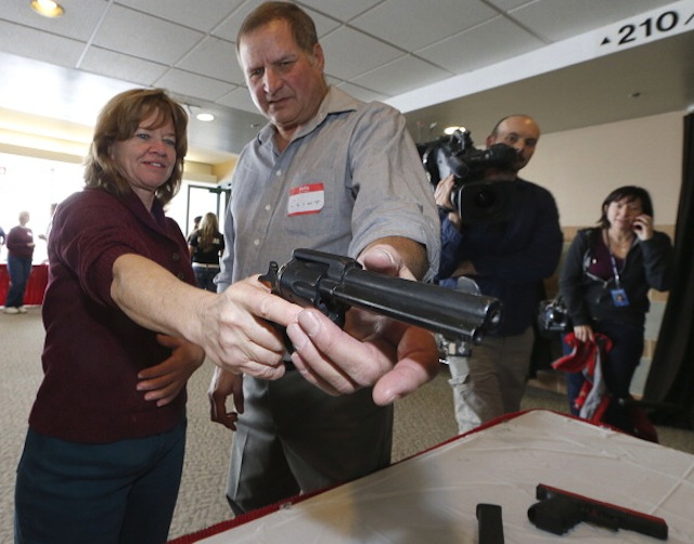 A Utah teacher is shown how to handle a handgun by instructor Clint Simon in West Valley City, Utah. (George Frey/Getty Images)