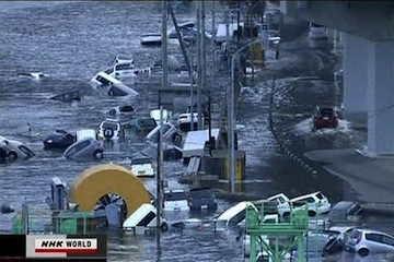 Cars floating away after March's quake (AP)