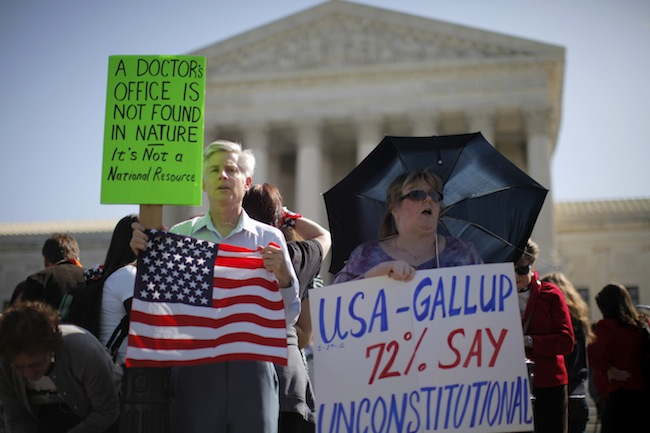 Two health care reform protesters on the first day of oral arguments. (Charles Dharapak/AP)