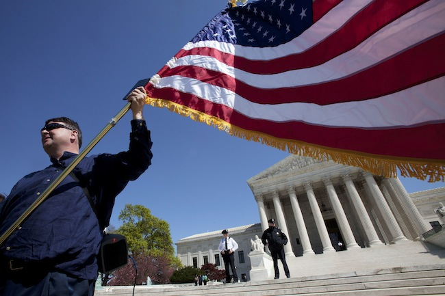 A protester in front of the Supreme Court on the second day of the health care law's oral arguments. (Jacquelyn Martin/AP)